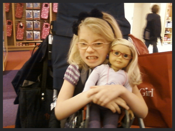 Young blond haired girl wih glasses and Koolen-de Vries Syndrome holding doll