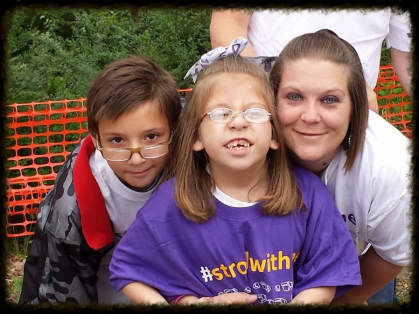 Smiling girl with Koolen-de Vries Syndrome with family