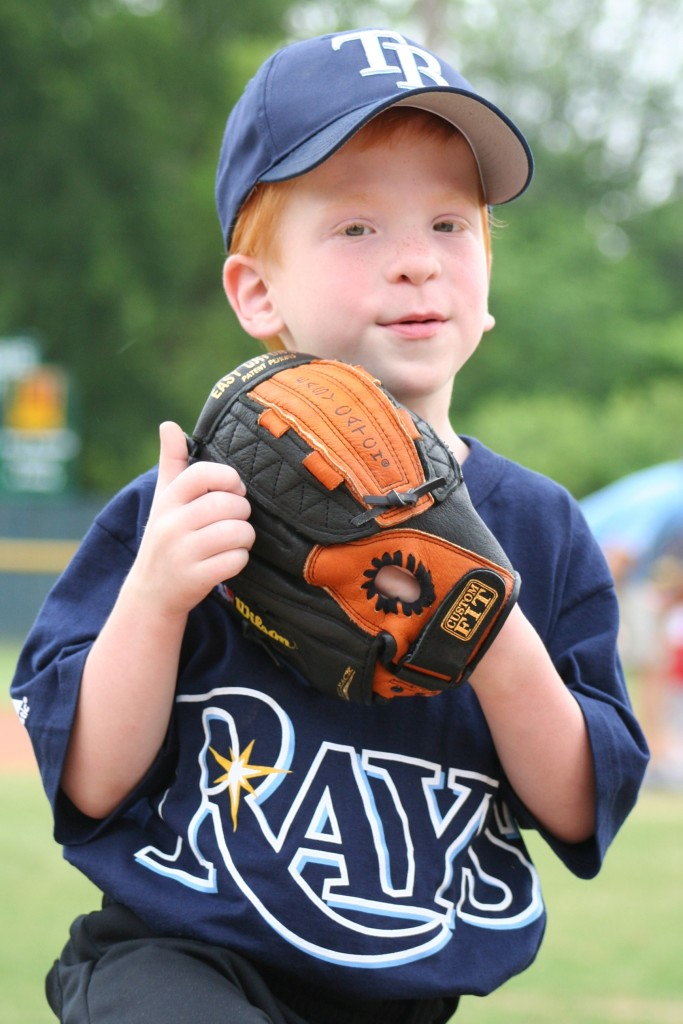 Young boy with Koolen-de Vries Syndrome holding baseball glove