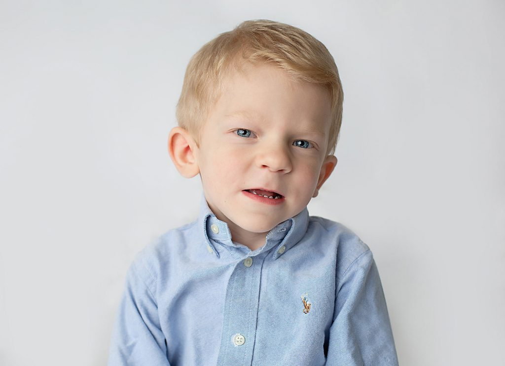 Blond haired blue eyed boy with Koolen-de Vries Syndrome wearning a blue shirt